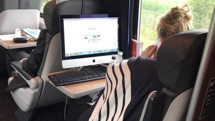 First Class Virgin Train becomes office as woman uses desktop computer